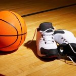 orange basketball ball next to basketball shoes