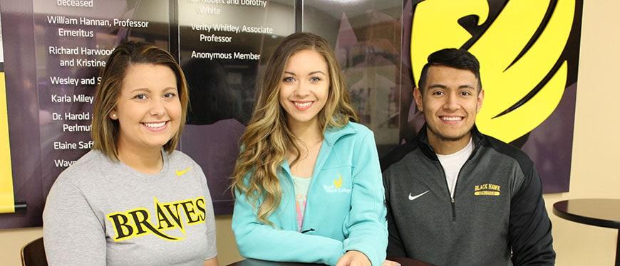Three students sitting outside the Hawk's Hub