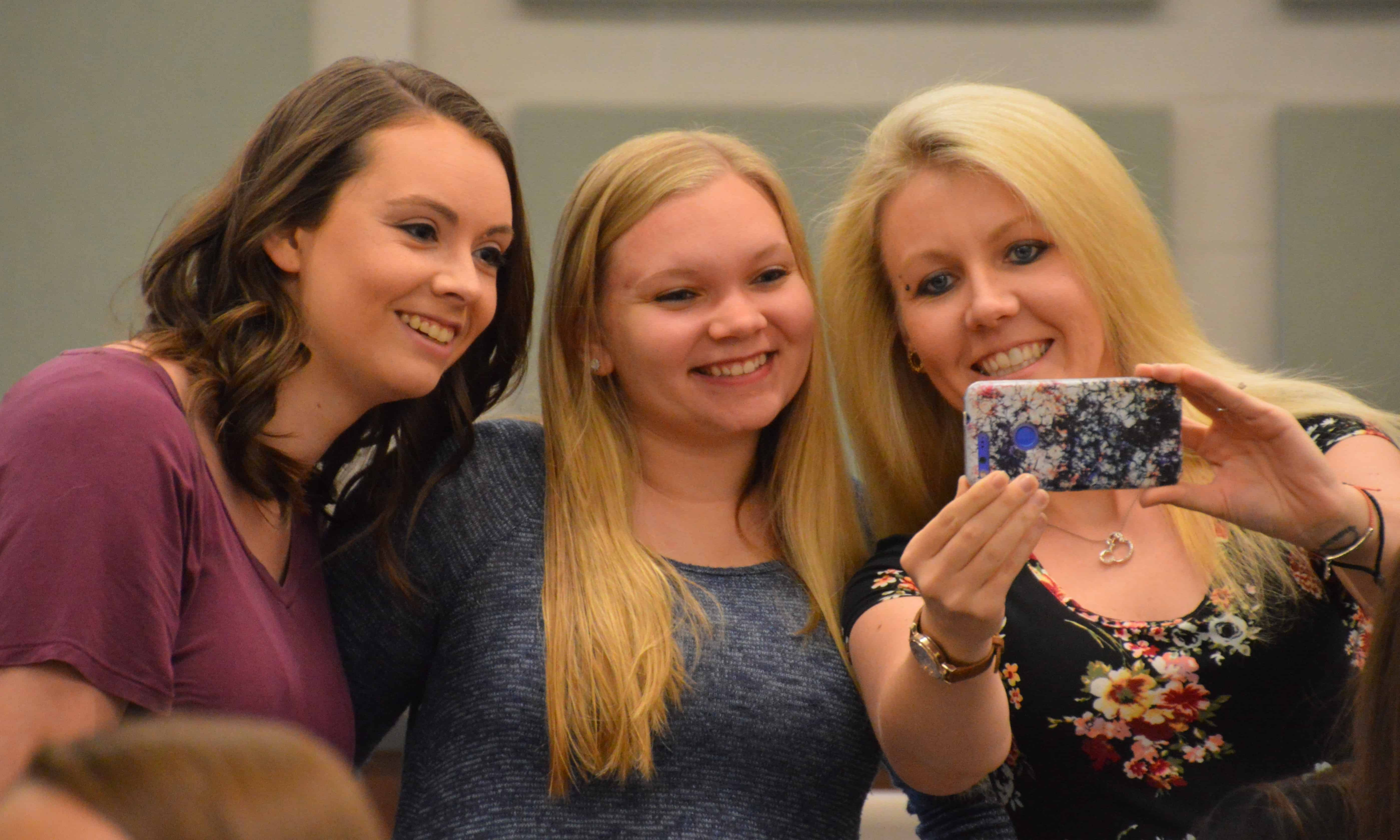 3 smiling female students taking selfie