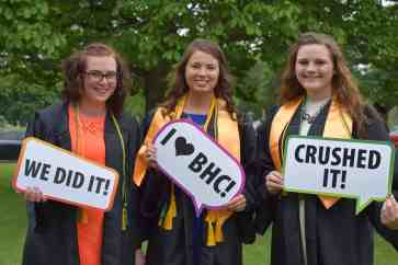 3 female graduates wearing gowns & holding signs at East Campus Commencement