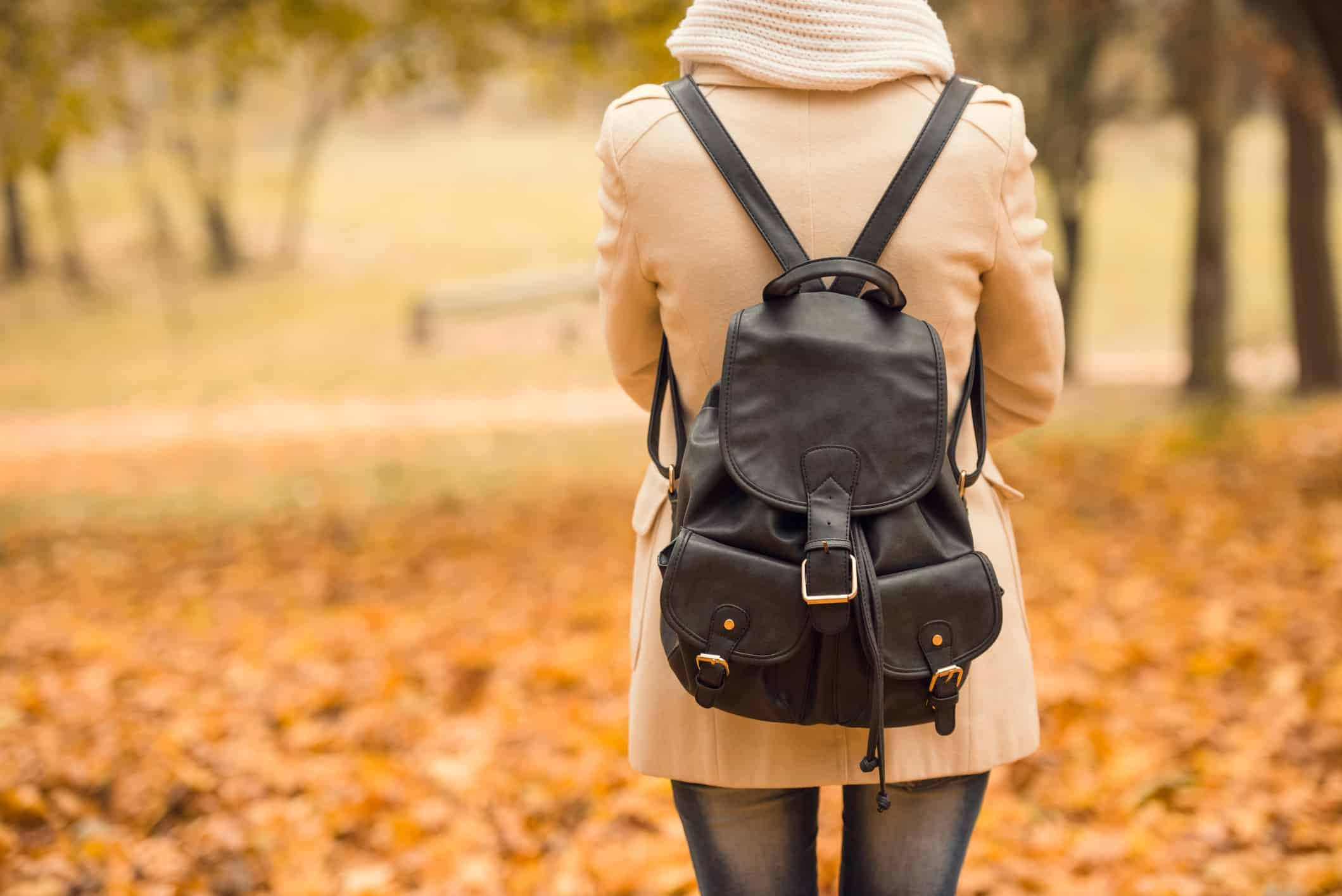 girl with bookbag walking in the autumn park