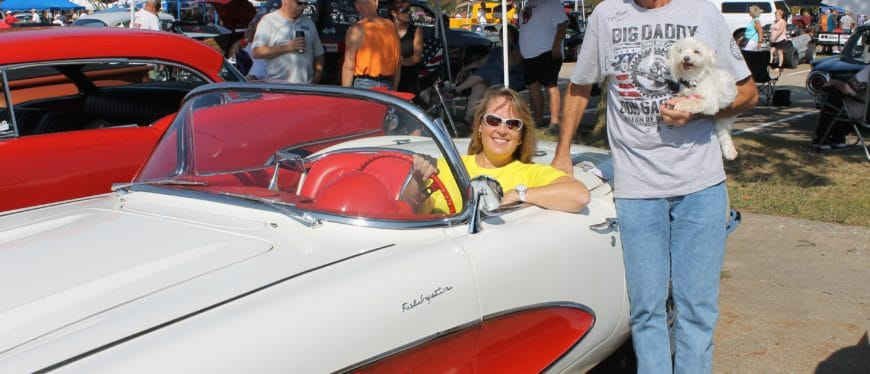 Bettie Truitt sitting in white & orange Corvette, Ron Williams standing next to car holding white dog