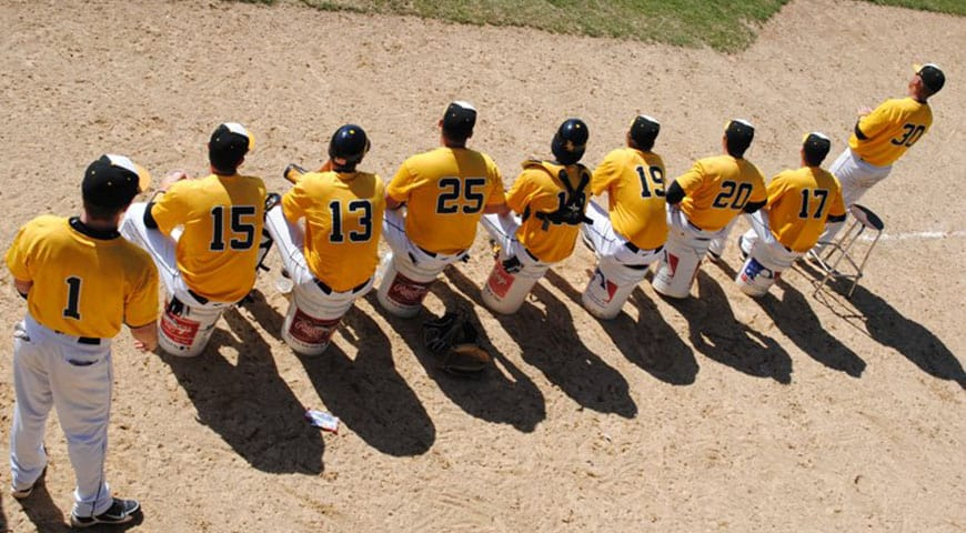 Baseball players sitting on buckets with backs to the camera