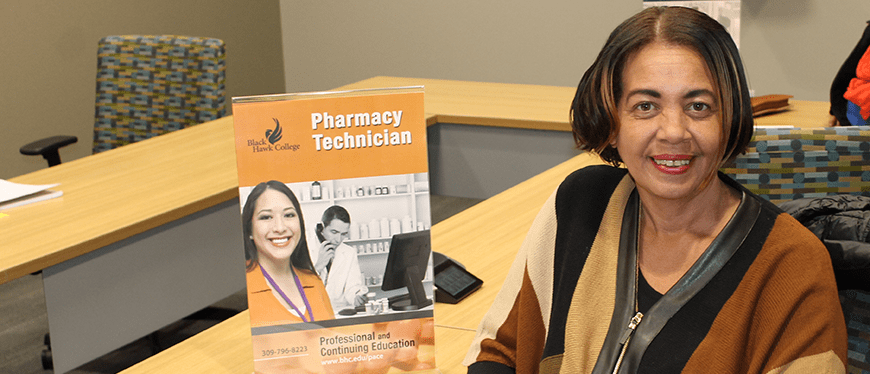 Pharmacy Tech professor sitting at a table to promote the program
