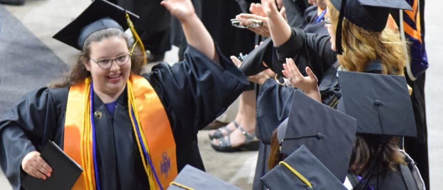 female grad giving high five