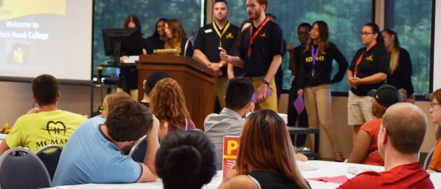 students speaking at podium