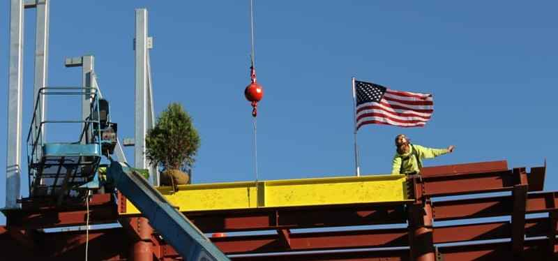 Closeup of yellow beam with evergreen & American flag and worker on top of red steel framework of new 2-story building