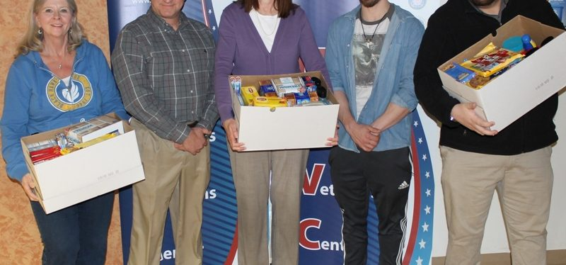 5 people looking at the camera with 3 holding boxes