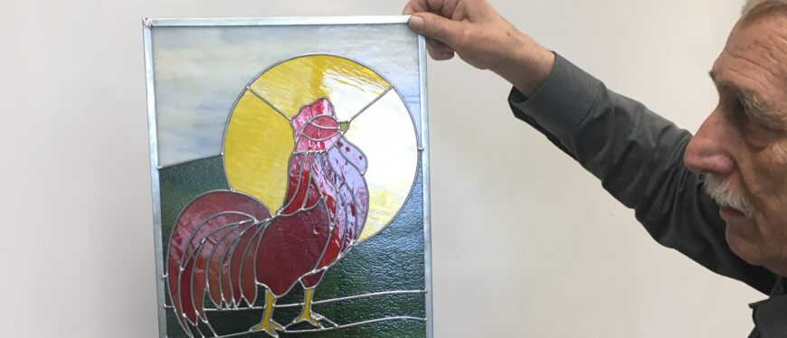 man holding stained glass art