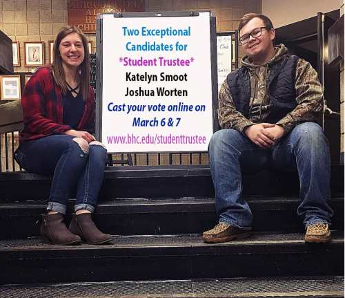 East campus student trustee candidates sit on stairs, one male one female.