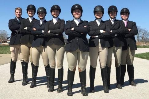 8 people wearing black riding helmets, black jackets, tan pants & black boots