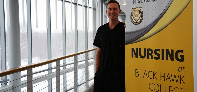 student posing near nursing sign