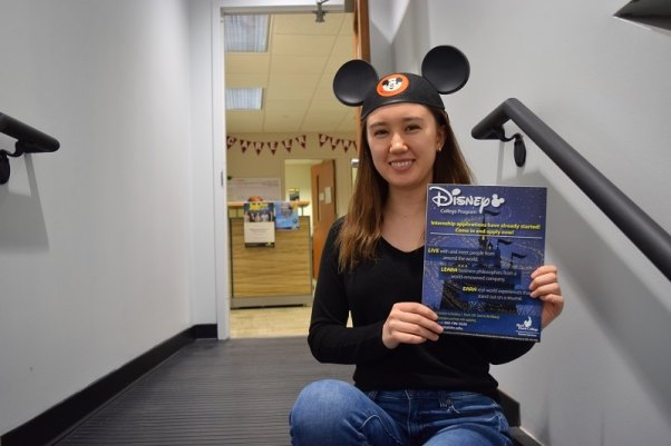 student wearing Mickey Mouse ears sits on a stair while holding a Disney internship flyer