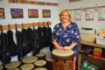 music teacher behind a drum with drums and ukuleles behind her