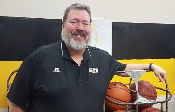 Darren Bizarri leaning on cage of basketballs