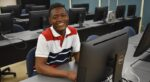 smiling male student sitting at a computer desk