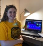 smiling student sitting at a desk while attending a virtual conference for Phi Theta Kappa