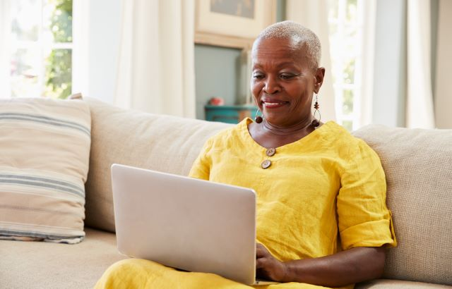 A stock photo of a woman using a laptop on her sofa