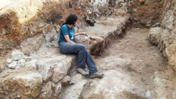 A young lady sits on the bench in the gate at Tel Lachish, leaning on the armrest. Photo by Sa'ar Ganor IAA