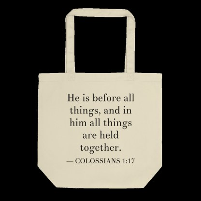 Oyster-colored bilingual tote bag with English (Colossian 1:17) flat on black background