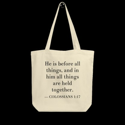 Oyster-colored bilingual tote bag with English (Colossian 1:17) on hanger with black background