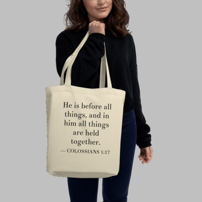 Oyster-colored bilingual tote bag with English (Colossians 1:17) held by woman