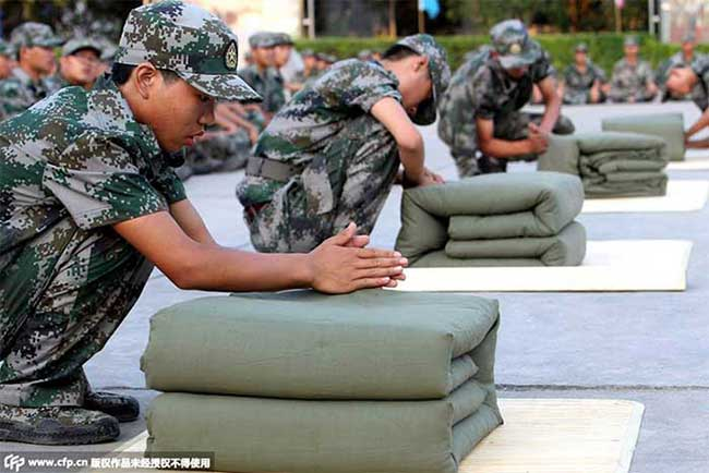 Chinese military trainees folding their stuff.