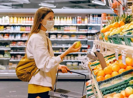 Woman wearing antiviral face mask in grocery store