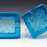 Beautiful 'pool blue' colored glass looks liquid and glitters and glows in the light. Perfect poolside or deck cigar ashtray set. They weigh 2 lbs each, can't get knocked around easily.