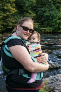 Helen cuddling her baby in a Tula carrier by a river