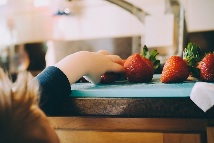 toddler sneaking strawberries off a chopping board