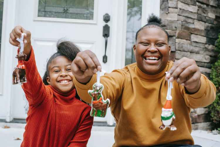 cheerful smiling children demonstrating christmas decorations they have found on the scavenger hunt