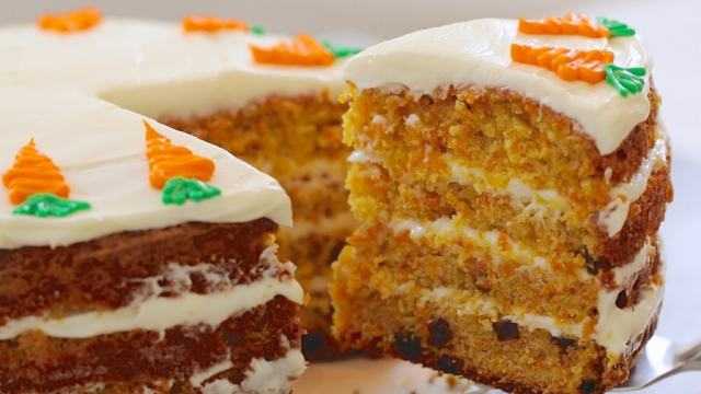 Best Ever Carrot Cake Recipe, finished and being served, showing all the layers and decorations.
