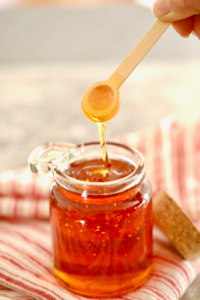 Golden Syrup Substitute dripping off a spoon into a jar, showing consistency.