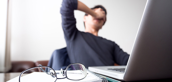man at desk with hand covering face taking a break from work with glasses and open laptop on desk symbolizing stress, frustration