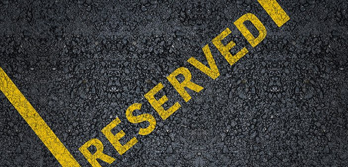Word reserved written with yellow paint on black asphalt