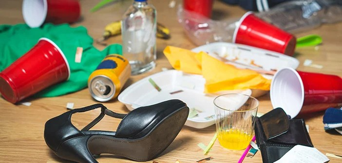 Terrible mess after party. Trash, bottles, food, cups and clothes on floor.