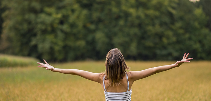 Woman with her back to the camera standing in autumn meadow with her arms spread widely as she enjoys the beauty of life and nature.