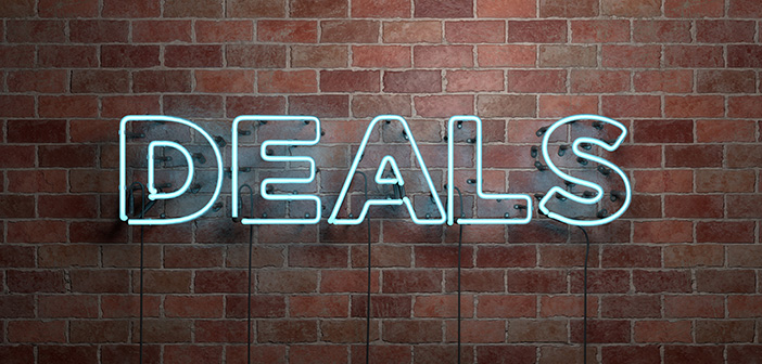 fluorescent neon sign reads deals on brick wall