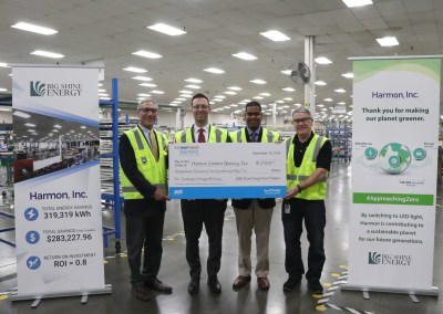 Harmon, Inc., BGE, and Big Shine representative pose with BGE incentive big check in Harmon's newly lit facility.