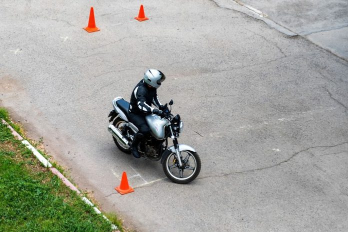 Person practising their motorcycling skills with orange cones around them