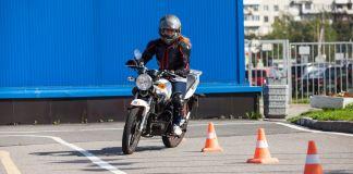 Learner motorcyclist riding slalom in between cones