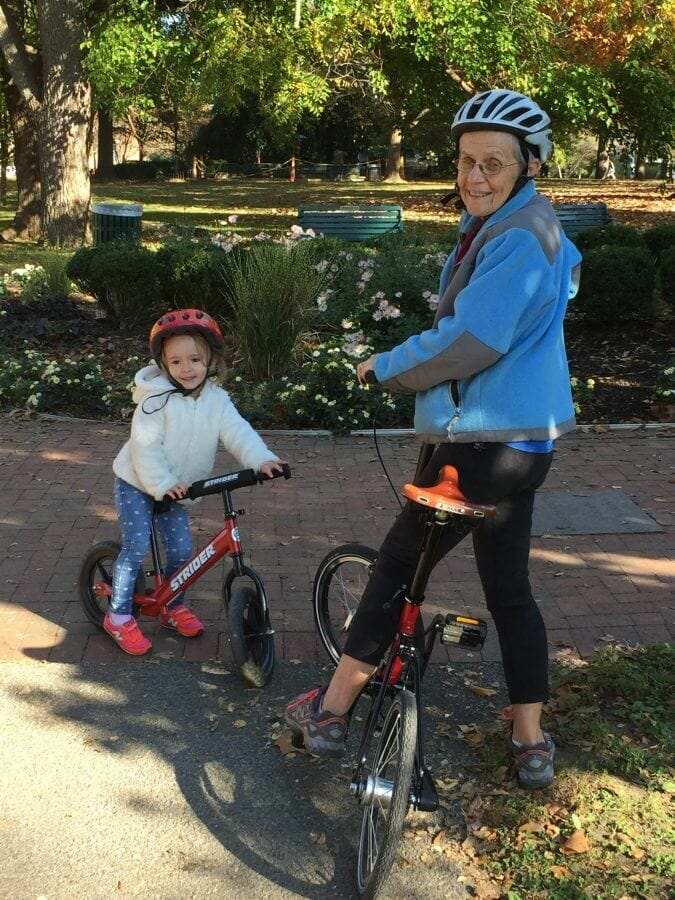 Grandma and granddaughter ride together in the city park