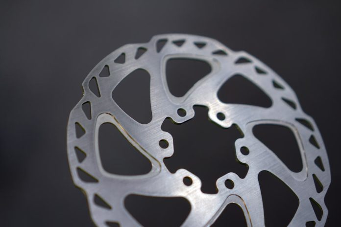 HCM multi-material disc brake rotor for road and mountain bikes with stainless steel braking surface over alloy center