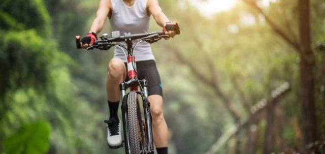 Mujer montando su bicicleta de montaña en el parque soleado