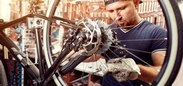 un hombre limpia la cadena de su bicicleta