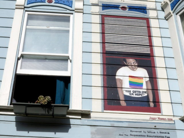 The Rainbow Honor Walk passes by the former site of Harvey Milk's camera shop, a center for activism in the '70s. A mural shows him looking out the window from his apartment above the shop. San Francisco, United States, North America.