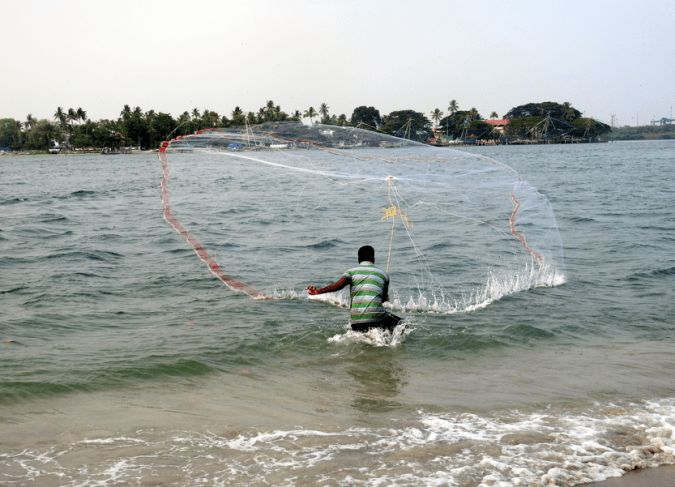 A fisherman casts a net at Fort Kochi's beach