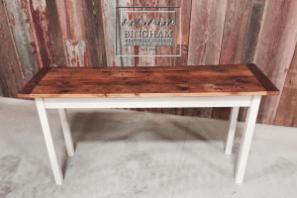 This table features a reclaimed pine top, displaying a natural texture and color, along with a painted pine base.