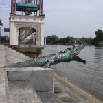 Crocodile statuary at the water's edge